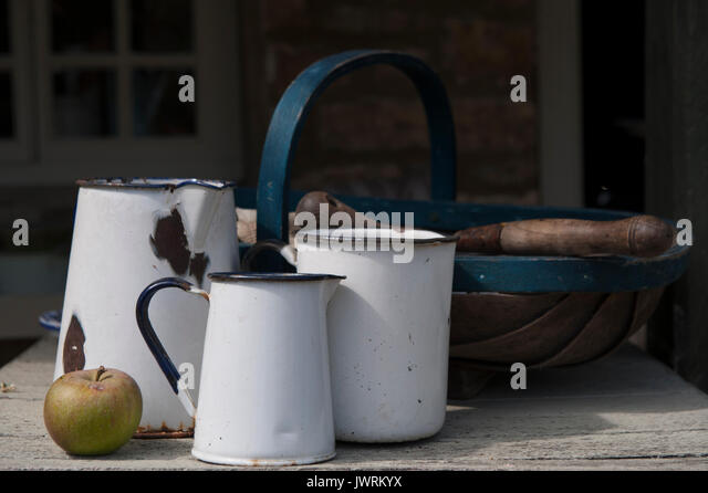 Enamel jugs on a table in an English country gardencountry - Stock Image
