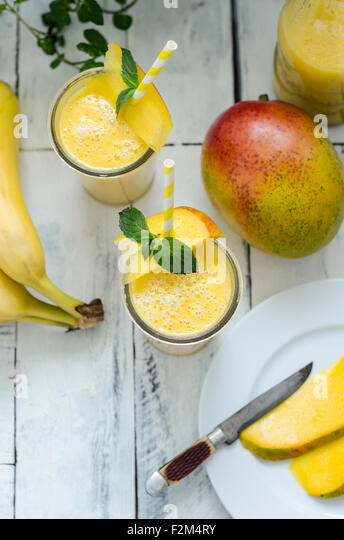 Two glasses of mango banana smoothie - Stock Image