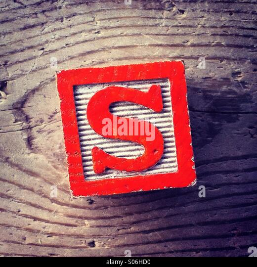 It's a woodblock toy with an alphabet letter on it: S - Stock Image