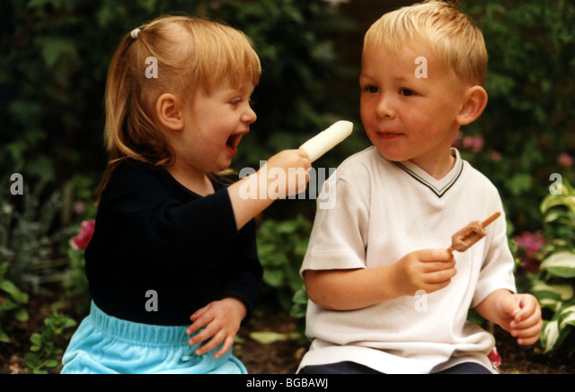 Photograph of playmates brother sister family lolly pop sharing - Stock-Bilder