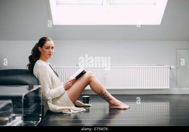 Beautiful brunette woman reading a book by a sofa. Attractive female model sitting on floor with a book looking - Stock-Bilder