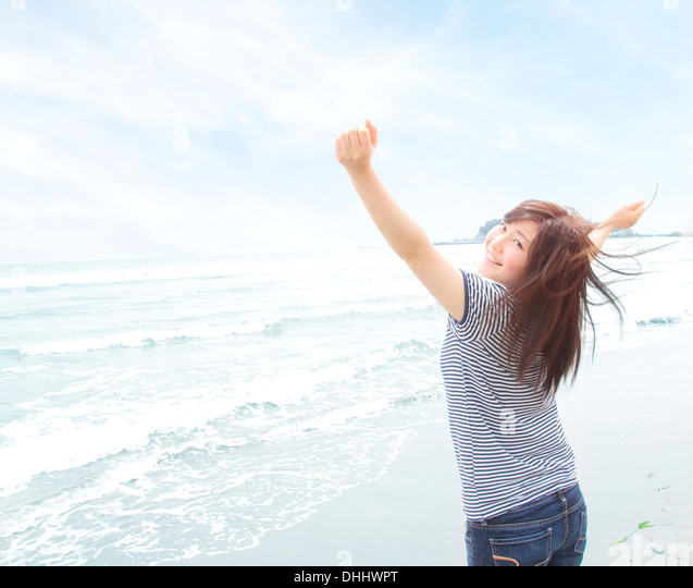 Portrait of young woman on beach with arms raised, looking over shoulder - Stock Image