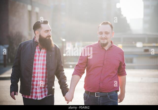 Gay couple walking hand in hand on street - Stock Image