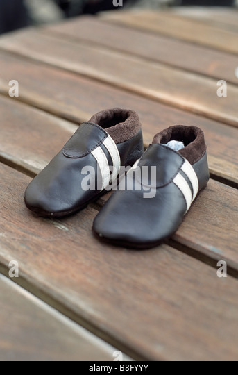 Leathery Children's Shoes on a wooden Underlay - Clothing - Childhood - Stock Image