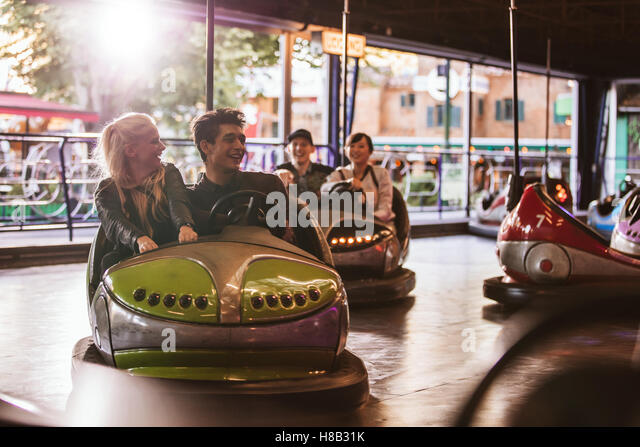 Young people driving bumper car at fairground. Young friends having fun riding bumper car at amusement park. - Stock Image