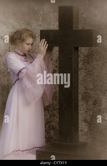 a woman in a pink wedding dress is standing next to a huge, black cross - Stock Image