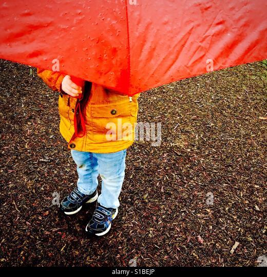 Little boy hides underneath a red umbrella - Stock Image