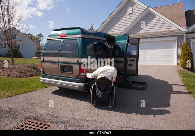 Man with spinal cord injury using magnetized remote to open his accessible vehicle - Stock Image