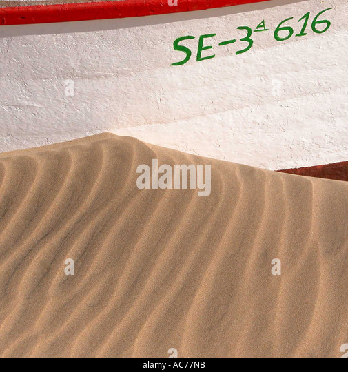 Blown sand against boat - Stock Image