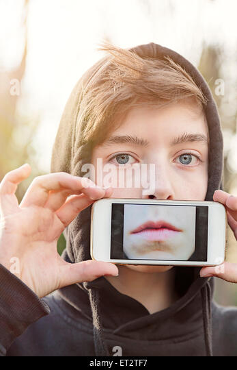 virtual realty, teenage boy holding a smart phone in front of his face - Stock Image