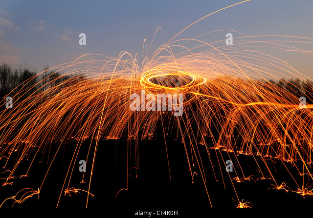abstract background with orange sparklers flying away at night time outdoor - Stock Image