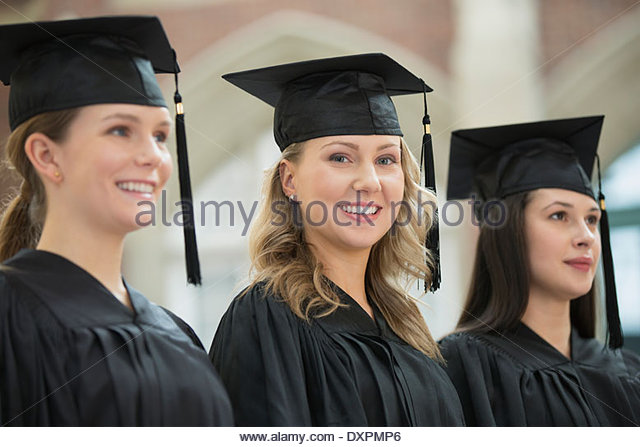 Portrait of happy college graduates standing in a row - Stock Image