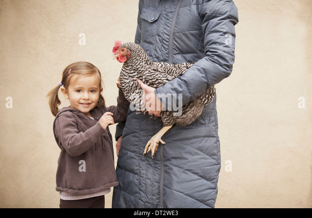 A woman holding a black and white chicken with a red coxcomb under one arm A young girl beside her holding her other - Stock-Bilder