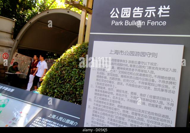 China Shanghai Huangpu District Nanjing Road People's Park entrance Park Bulletin Fence rules Mandarin symbols - Stock Image