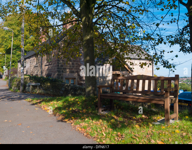 Wooden Bench next to a tree in the village of Holbrook, Derbyshire, United Kingdom. - Stock Image