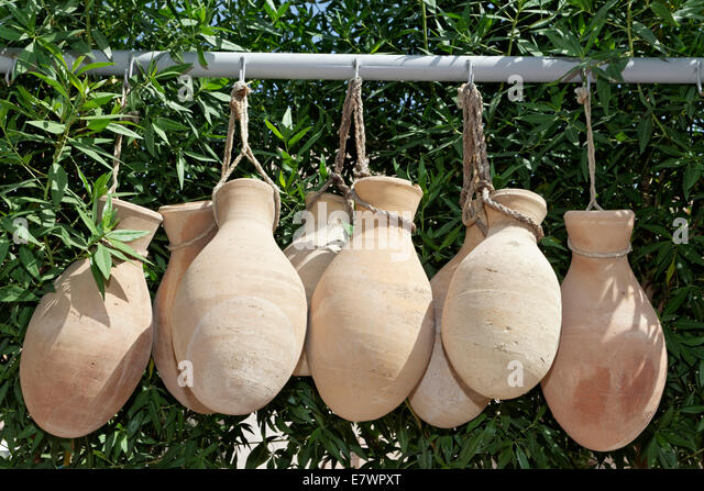 Clay jugs hanging in front of oleander shrubs, Nakhl Fort or Husn Al Heem, Al-Batinah province, Sultanate of Oman - Stock Image