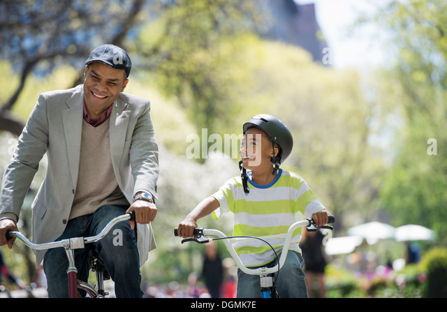 A family in the park on a sunny day. Father and son bicycling - Stock-Bilder