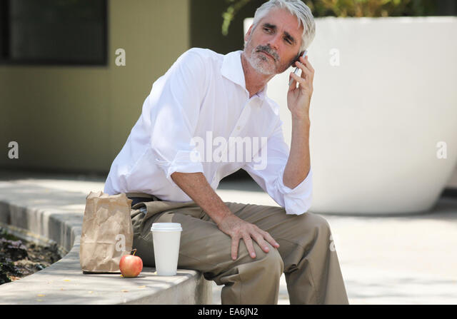 Businessman on lunch break talking on phone - Stock Image