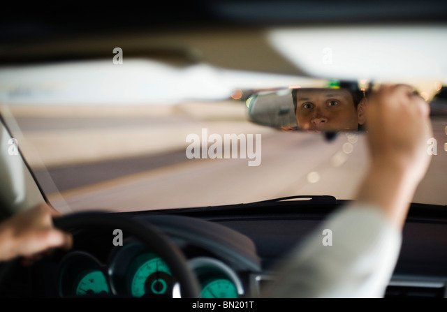 Driver driving adjusting rearview mirror - Stock Image
