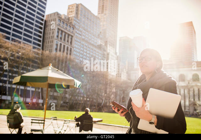 Businesswoman listening music while waiting at Bryant Park against buildings - Stock-Bilder