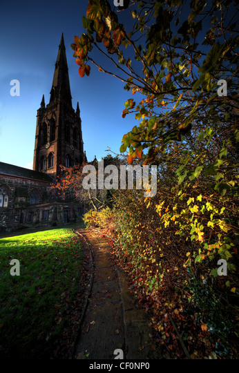 Up the path to Warrington St Elphins church showing its spire on an autumn morning - Stock Image
