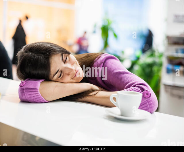 Young businesswoman sleeping at desk in office - Stock Image