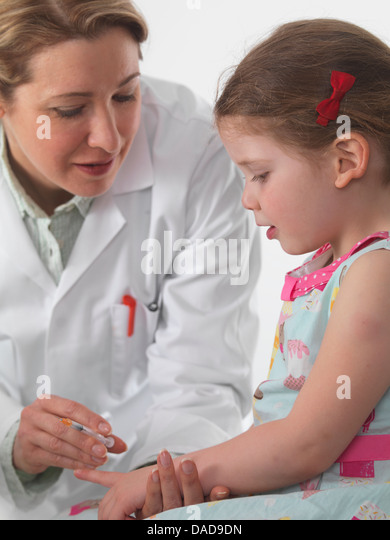 General practice doctor vaccinating a small girl in surgery - Stock Image