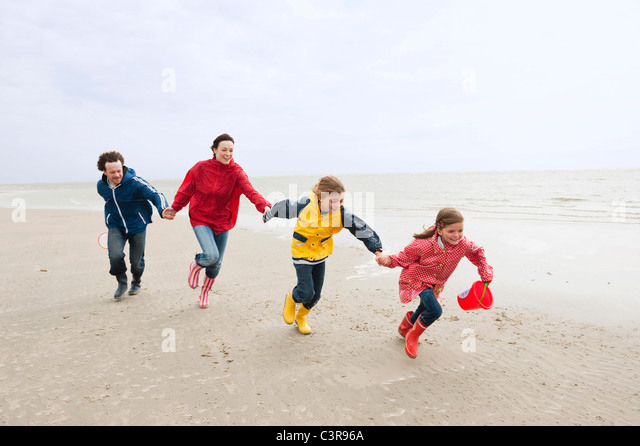Germany, St. Peter-Ording, North Sea, Family holding hands and running on beach - Stock-Bilder