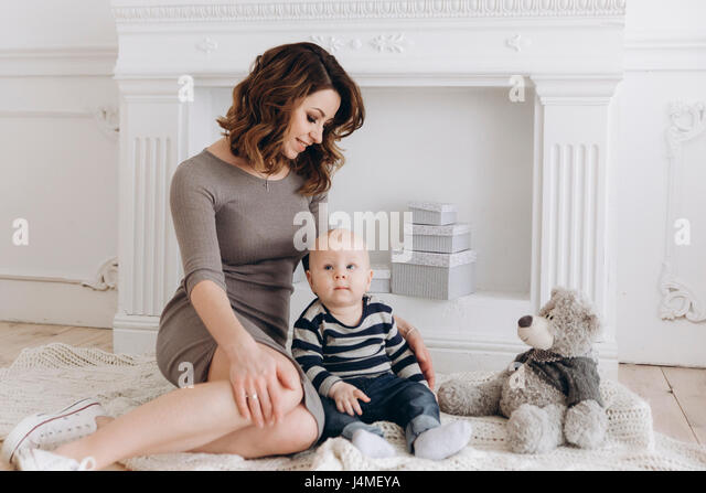 Caucasian mother sitting on floor with baby son - Stock-Bilder