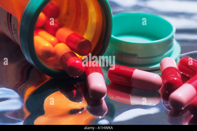 Capsules Spilling Out Of Container Sandra Baker - Stock Image
