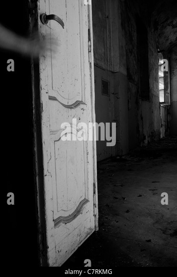 Hand on a door in abandoned manor room - Stock Image