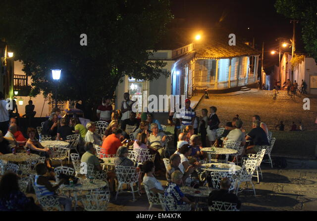 People sitting at an outdoor bar on a square in Trinidad, Cuba, Caribbean, Latin America - Stock Image