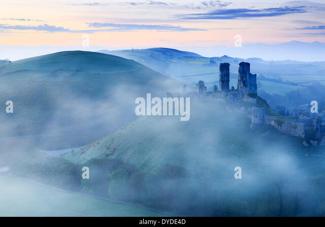 Corfe Castle in Dorset rising above early morning mist. - Stock Image
