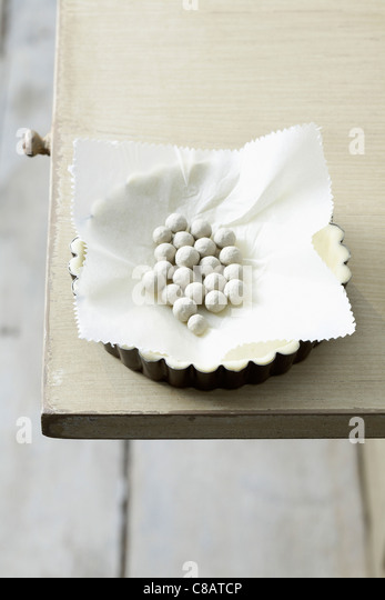 Cooking the pastry base in the mould with marbles - Stock Image