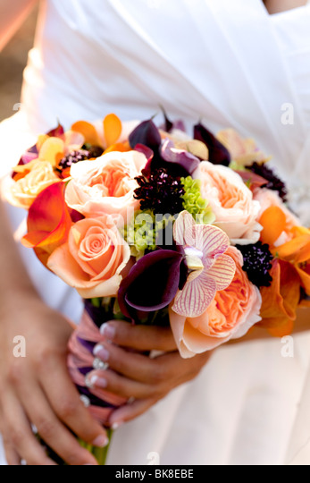 bride bouquet, colorful flowers orange, purple, peach, yellow, white - Stock Image