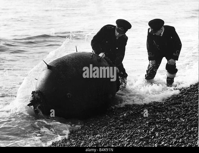 WW2 Sea Mines December 1945 Two Royal Navy lieutenant commanders defuse a mine on Rye Beach - Stock Image