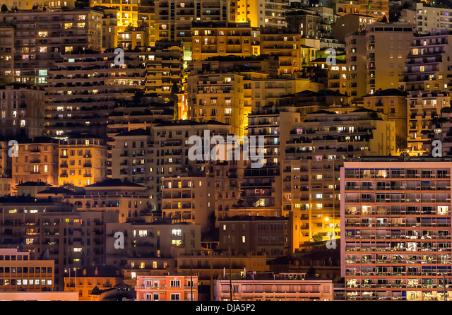 Dense cluster of city buildings at night. - Stock Image