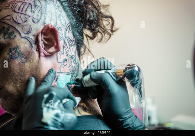 A tattoo artist from Brazilian Crew works on a neck tattoo at the 17th International Barcelona Tattoo Expo. 3rd - Stock-Bilder