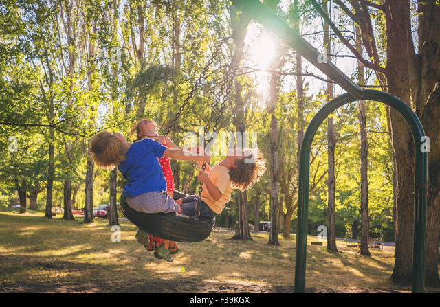 Three children playing on a swing - Stock Image