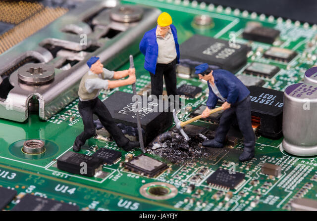 miniature workers on a computer mainboard - studio shot - Stock Image