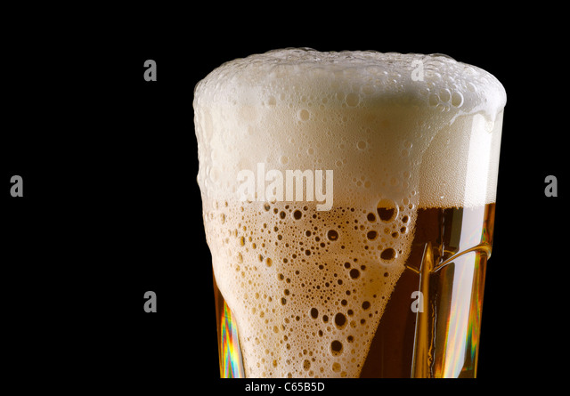 Overflowing glass of beer - Stock Image