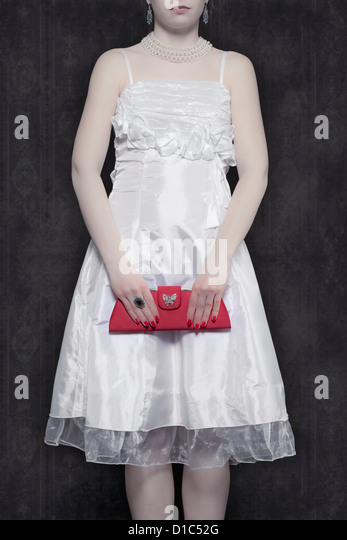 detail view of a woman in a white dress with a red handbag - Stock Image