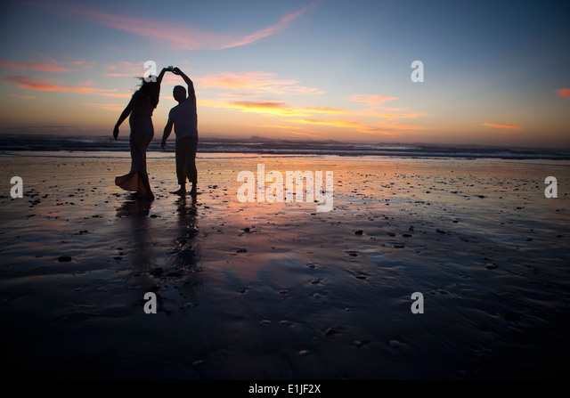 Couple dancing on beach at sunset, Cape Town, South Africa - Stock Image