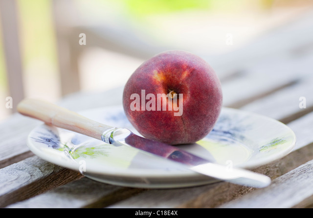 Peach on a plate with knife - Stock Image
