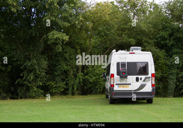 Rear view of camper van in a pleasant rural setting - Stock Image