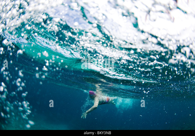 Underwater view of a swimmer enjoying a relaxing swim in the tropical waters off of the Yasawas Islands, Fiji. - Stock Image
