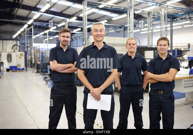 Portrait of four workers in engineering factory - Stock Image