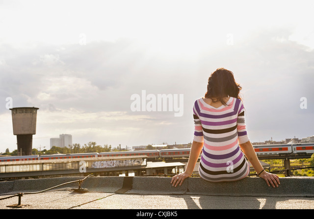 Germany, Hamburg, Young woman sitting at edge of roof - Stock Image