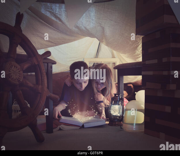 Two young children are reading a book together with sparkles in a tent fort at home for a storytime or learning - Stock Image
