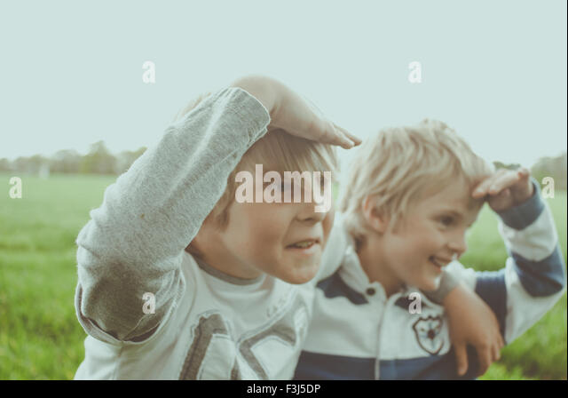 Two little brothers playing in a field - Stock Image